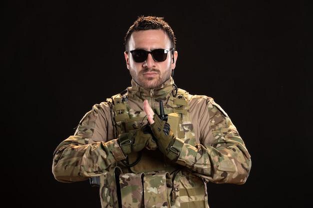 Coole mannelijke soldaat in camouflage op zwarte muur
