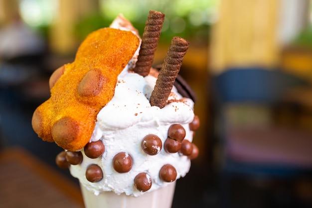 Coole milkshake met koekjes en chocoladeballetjes. milkshake in een bekerglas van glas op een tafel op een straat platform in een café. verfrissende zomerdrankjes.