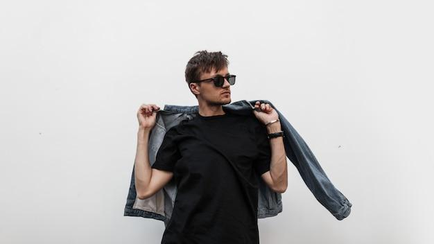 Coole moderne jonge hipster man met een stijlvol kapsel in zonnebril in een zwart t-shirt trekt een vintage blauw denim jasje aan. aantrekkelijke stedelijke man poseren in de buurt van een witte muur. modieuze lente herenkleding.