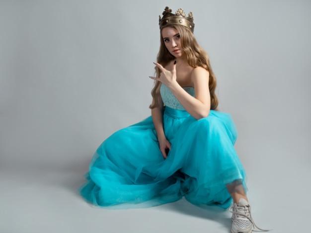 Coole prinses in een weelderige blauwe jurk en kroon maakt een rocker handgebaar
