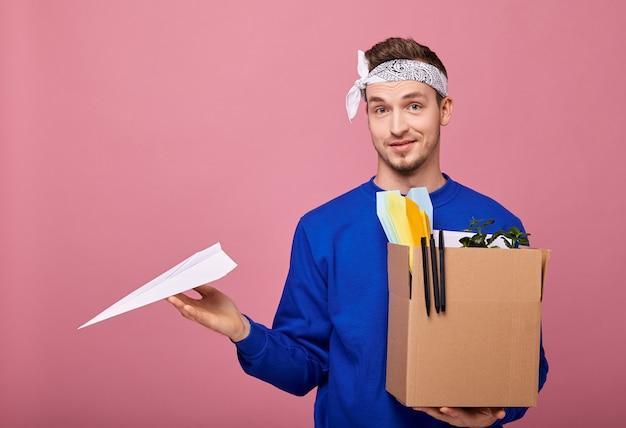 Coole retro man in witte bandanwith doos en papieren vliegtuigje in handen na ontslagen te zijn