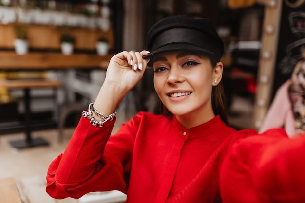 Coole selfie tegen de achtergrond van een straatcafé. jong meisje gekleed in een stijlvolle rode zijden outfit met zilveren armbanden en oorbellen in de vorm van parels lacht