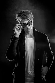 Coole stijlvolle man in zwarte jas en zonnebril