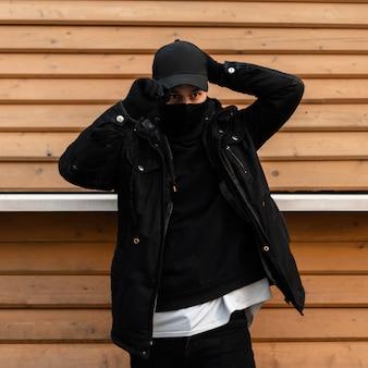 Coole stijlvolle man met een zwart beschermend masker in zwarte modekleding draagt een zwarte pet bij een houten muur