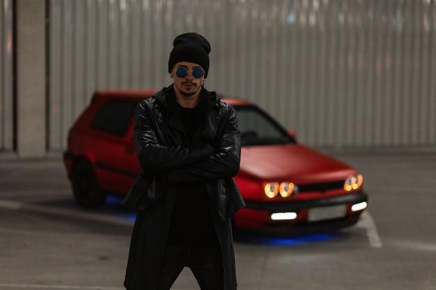 Coole stijlvolle man met mooie zwarte bril en een hoed in een leren jas en hoodie staat 's nachts buiten op een parkeerplaats
