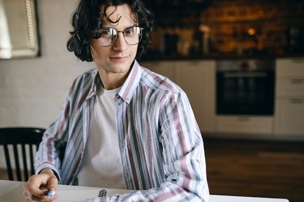 Coole student met stijlvolle bril doet thuisopdracht aan bureau, maakt aantekeningen, luistert naar muziek via draadloze hoofdtelefoons. aantrekkelijke jonge mannelijke artiest met koptelefoon schetsen in notitieblok, glimlachend