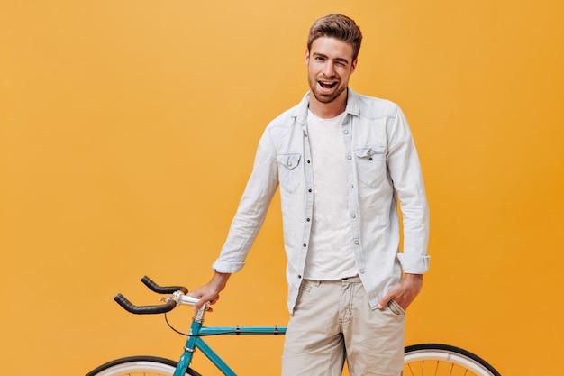 Coole trendy man met bruin haar in stijlvolle lichte kleding die knipoogt, lacht en poseert met een fiets op een geïsoleerde oranje muur