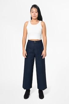 Coole vrouw in witte tanktop en zwarte a-lijn broek street fashion full body