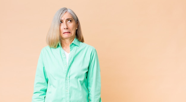 Coole vrouw van middelbare leeftijd die bezorgd, gestrest, angstig en bang kijkt, in paniek raakt en tanden op elkaar klemt