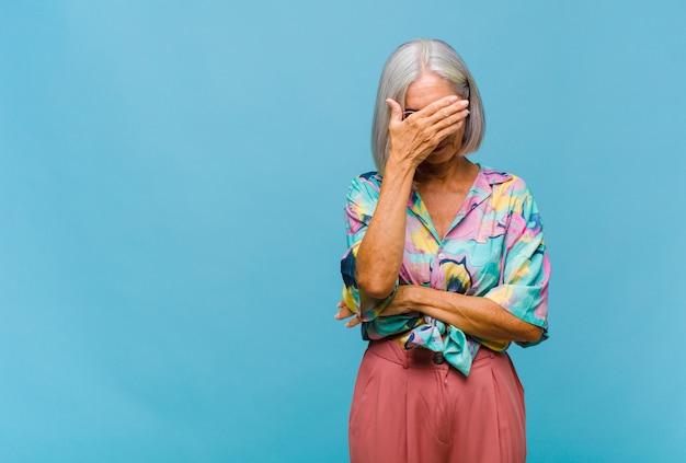 Coole vrouw van middelbare leeftijd die gestrest, beschaamd of boos kijkt, met hoofdpijn, gezicht bedekt met hand