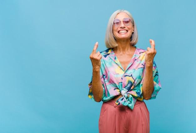 Coole vrouw van middelbare leeftijd die lacht en angstig beide vingers kruist, zich zorgen maakt en geluk wenst of hoopt