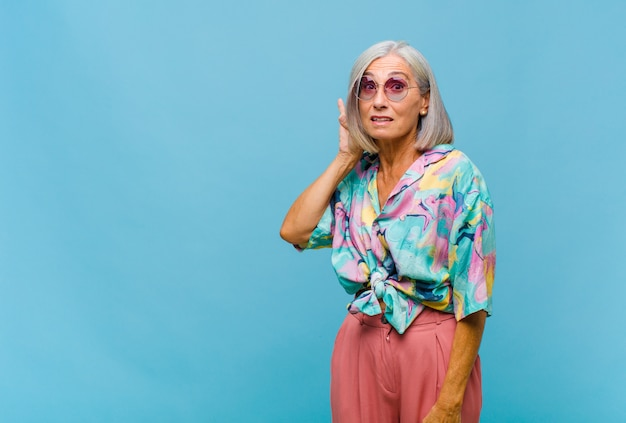 Coole vrouw van middelbare leeftijd die lacht, nieuwsgierig naar de zijkant kijkt, probeert te roddelen of een geheim afluistert