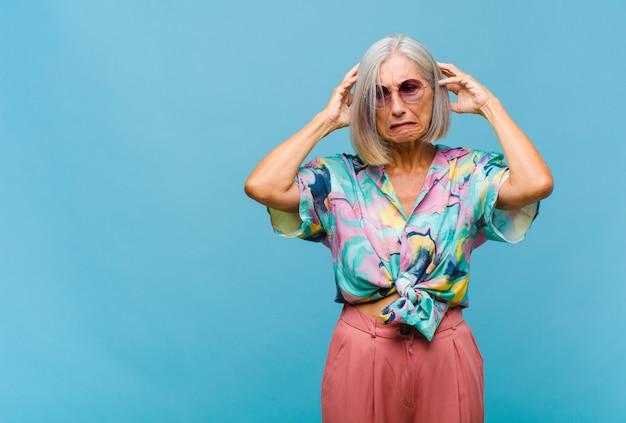 Coole vrouw van middelbare leeftijd die zich gefrustreerd en geïrriteerd voelt, ziek en moe is van mislukking, beu is met saaie, saaie taken