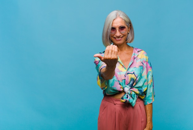 Coole vrouw van middelbare leeftijd die zich gelukkig, succesvol en zelfverzekerd voelt, een uitdaging aangaat en zegt: kom maar op! of je verwelkomen