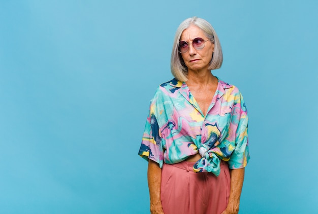 Coole vrouw van middelbare leeftijd die zich verdrietig, boos of boos voelt en opzij kijkt met een negatieve houding, fronst bij onenigheid
