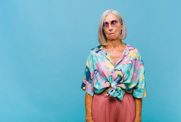 Coole vrouw van middelbare leeftijd die zich verward en twijfelachtig voelt, zich afvraagt of probeert te kiezen of een beslissing neemt