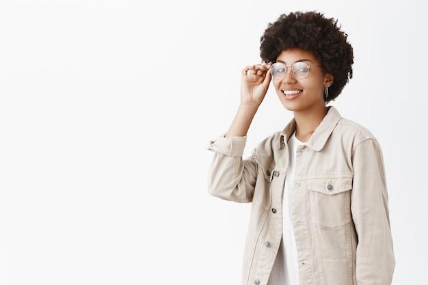 Coole, zelfverzekerde en stijlvolle jongensachtige vrouw met afrokapsel die de rand van de bril op de ogen aanraakt en breed glimlachend zelfverzekerd is en klaar om een nieuwe werkdag uit te dagen