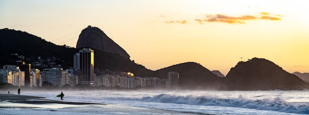 Copacabanastrand in rio de janeiro met de suikerbroodberg bij zonsondergang