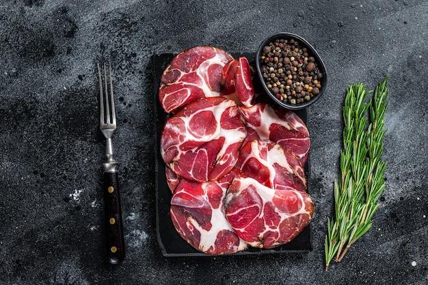 Coppa, capocollo, capicollo gerookte ham op marmeren bord. zwarte achtergrond. bovenaanzicht.