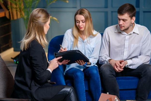 Copule van jonge cliënten die contract ondertekenen voor het kopen van nieuw huis, vlak.