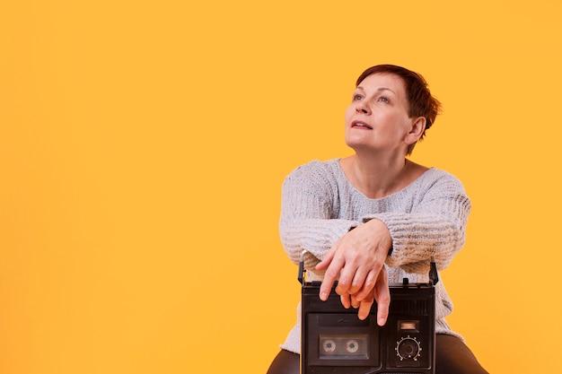 Copy-space dromerige senior vrouw met cassette