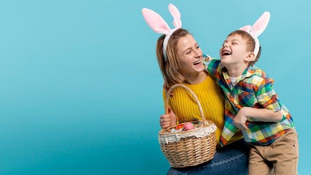 Copy-space gelukkige moeder en zoon met mandje met beschilderde eieren