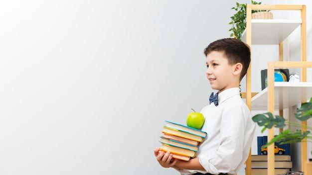 Copy-space jongen die stapel boeken draagt
