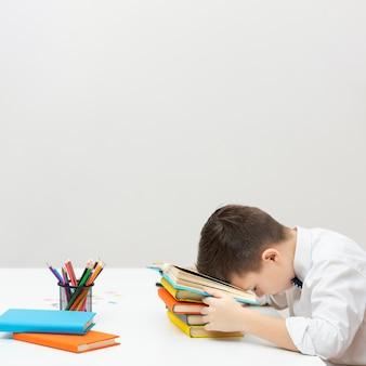 Copy-space jongenszitting met hoofd op boeken
