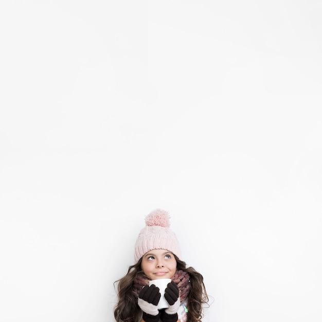 Copy-space klein meisje in de winter het drinken van thee