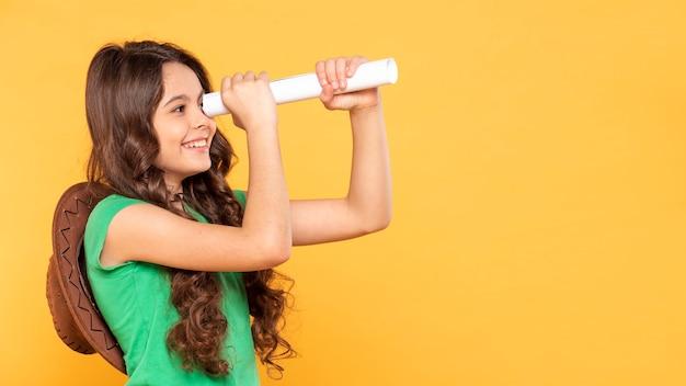 Copy-space meisje met verrekijker papier