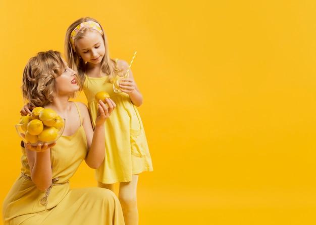 Copy-space moeder en dochter met citroenen
