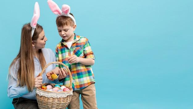 Copy-space moeder en zoon kijken naar mand met eieren