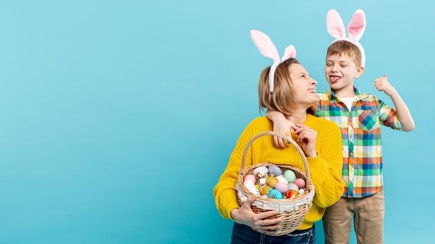 Copy-space moeder en zoon met een mand met eieren voor pasen