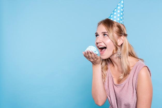 Copy-space speelse vrouw die cake eet