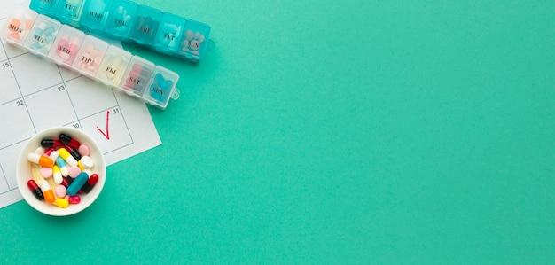Copy-space tabletten met dagelijkse pillen op het bureau