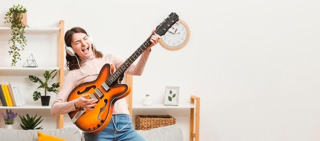 Copy-space vrouw op de bank met gitaar