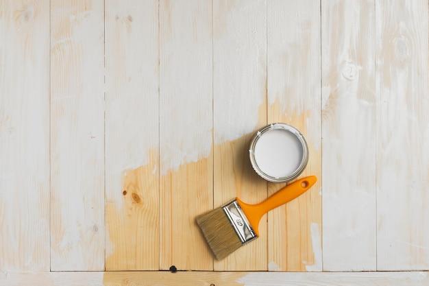 Copyspace met penseel en kan liggen op gedeeltelijk geschilderde houten achtergrond. bovenaanzicht.