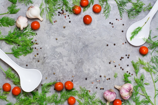 Copyspacekader van kers, dille, peperkruid, knoflook en gietlepels op een grijze achtergrond. bovenaanzicht
