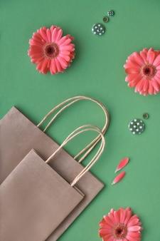 Coral gerbera madeliefjebloemen en ambachtelijke papper boodschappentassen op groenboek oppervlak,