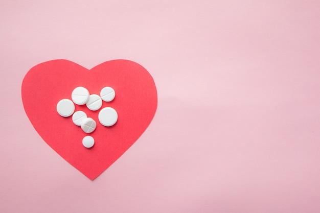 Corazon de papel con pildoras de medicina en fondo rosa