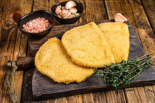 Cordon bleu vleeskoteletten met broodkruimels op een houten bord