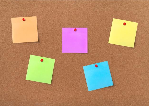 Cork board met kleurrijke blanco notities met uitknippad