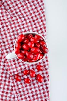 Cornel bessen in een beker op picknickdoek en wit