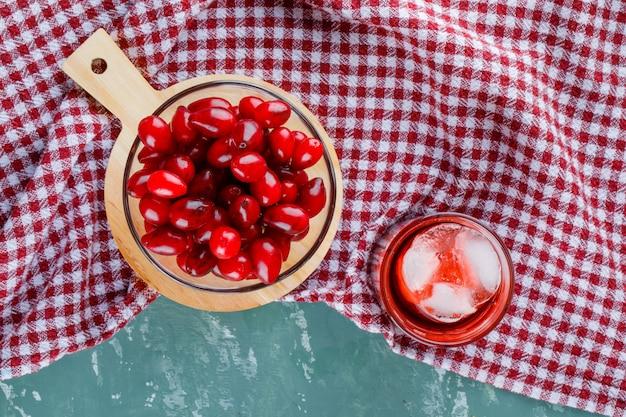 Cornel-bessen in een kom met drank, snijplank op gips en picknickdoek