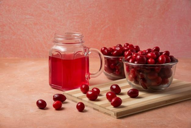 Cornels in glazen beker en sap in een pot op een roze achtergrond.