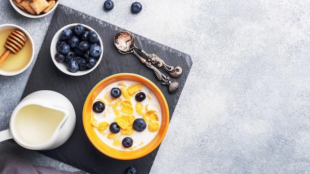 Cornflakes gemaakt van natuurlijke granen met verse bosbessen, honing en melk. het concept van een gezond gezond ontbijt. kopieer ruimte grijze betonnen tafel