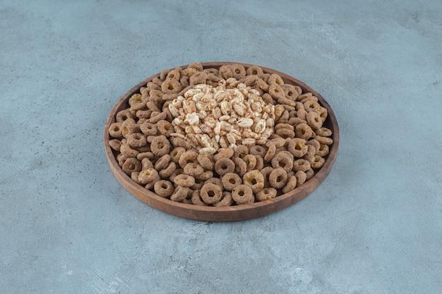 Cornflakes in de houten plaat, op de blauwe achtergrond. hoge kwaliteit foto
