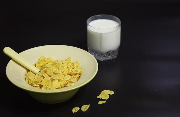 Cornflakes in een bord. ontbijt van vlokken met honing en melk. snel ontbijt met cornflakes