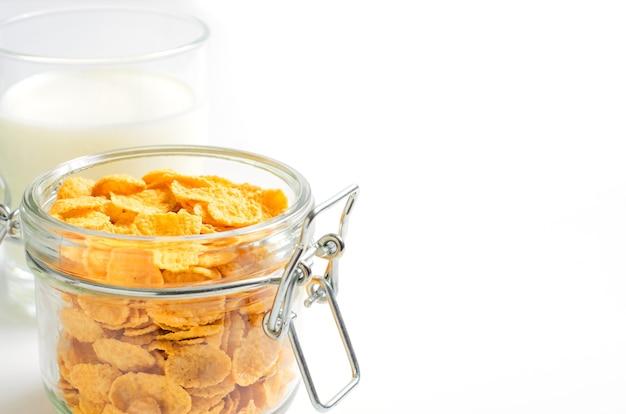 Cornflakes in een glazen container en melk op wit