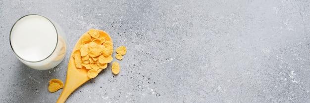 Cornflakes in een houten lepel, melk in een glazen beker. het concept van een gezond ontbijt. kopieer ruimte.